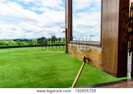 Opened Wooden Windows for Green Field and Cloudy Sky