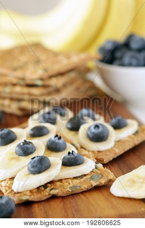 Banana And Blueberries On Pumpkin Seeded Crackers - Shallow Dof