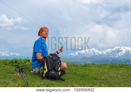 Happy Traveler Sits On The Alpine Meadow With A Tablet Computer