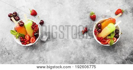 Multi-colored Popsicles With Strawberry, Red Currant And Cherry On A Gray Background. Top View, Copy