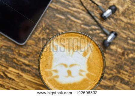 Cute cat latte art. Coffee glass and earphones. Songs to start the day.