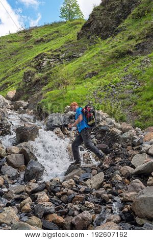 Bearded Man Adventurer With Backpack Is Preparing To Jump Over A Mountain River
