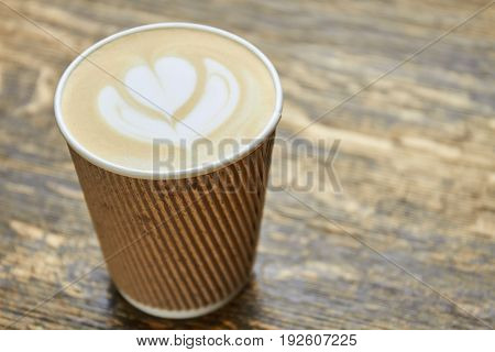 Latte art in paper cup. Coffee foam flower symbol.