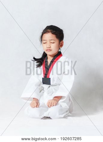 Asian little girl is sitting for concentration in taekwondo uniform on white background with copy space