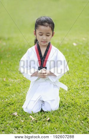Asian little sitting on green grass field close her eyes with concentration in taekwondo uniform shallow depth of field Thai girl