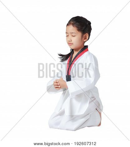 Happy Asian little girl is sitting for concentration in taekwondo uniform isolated on white background with clipping path copy space