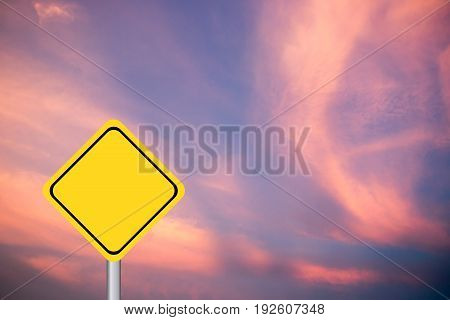 Blank yellow diamond transport sign on purple and pink sky background