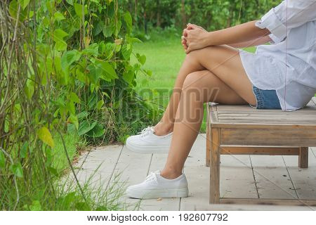 Relaxation Concept : Woman relaxing on wooden chair at outdoor garden surrounded green natural.