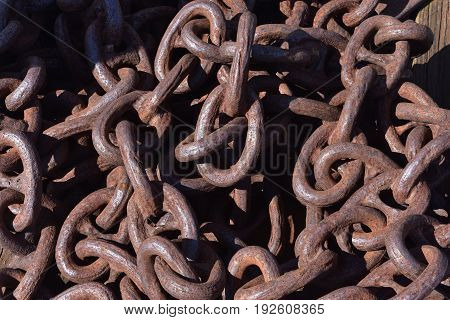 Rusting and corroding heavy link chain in a large pile.