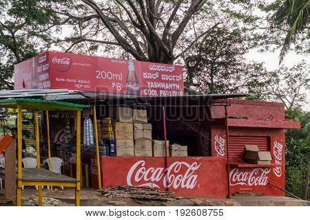 Mysore India - October 26 2013: Red Coca-Cola booth selling drinks at holy Sangam Ghat on Srirangapatna Island in the Cauvery River. Trees in background.
