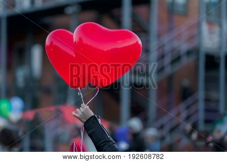 Two LED balloons in the form of scarlet burning hearts in the evening in the girl's hand. For a romantic background, for example, in the day of Valentine's Day