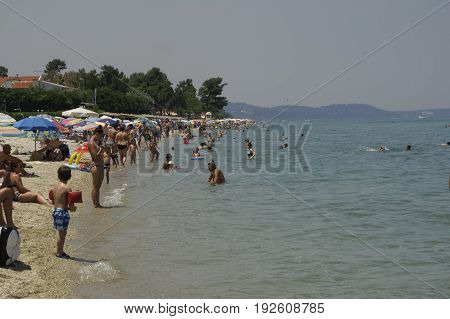 Chaniotis, Greece. June 24 2017: locals and tourists on the beach on a hot day. Heatwave temperatures lead hundreds of people on the beach at Chalkidiki peninsula.