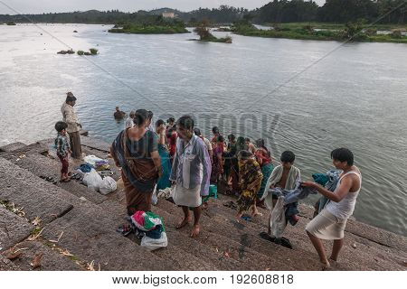Mysore India - October 26 2013: People gather for bathing and Final farewell rituals at Sangam Ghat on Srirangapatna Island at confluence of two arms of Cauvery River. People on stairs. Green shores.