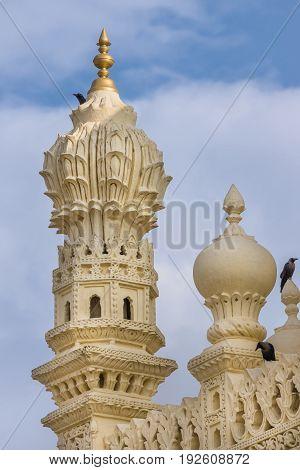 Mysore India - October 26 2013: Cream yellow stone corner minaret of upper structure Tipu Sultan mausoleum with black birds. Golden Kalasam on top blue cloudy sky.