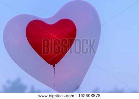 Red LED Balloon in forme Heart and additional silhouette of the heart in the sky at night. Romantic style love concept, Valentine's holiday. Background with place for your text