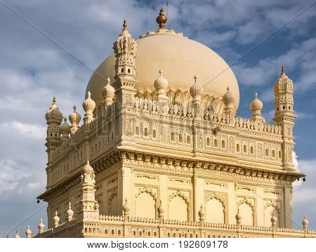 Mysore India - October 26 2013: Upper structure and dome of cream yellow Tipu Sultan mausoleum under blue cloudy sky. Golden Kalasam on top.