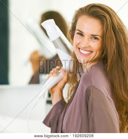 Portrait Of Smiling Young Woman With Blow Dryer In Bathroom