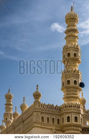 Mysore India - October 26 2013: Cream yellow minaret and part of upper structure of mosque at Tipu Sultan mausoleum under blue sky. Sound system.