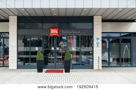 BRISTOL UNITED KINGDOM - MAR 8 2017: ibis hotel entrance welcome door with red signage and designed trees and red carpet - clean hotel with luxury entrance - Ibis Bristol Centre Harbourside