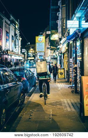 OXFORD UNITED KINGDOM - MAR 2 2018: Rear view of man with logotype of Deliveroo delivery bike in city of Oxford UK. Deliveroo is a British online food delivery company with operations spread across eighty-four cities in the UK the Netherlands France Germa