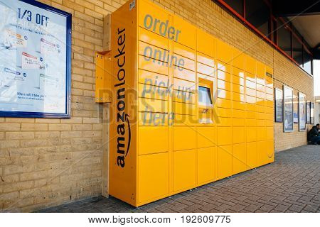OXFORD UNITED KINGDOM - MAR 2 2017: Side view of Amazon locker orange delivery package locker in public place at the train station in Oxford - Amazon Locker is a self-service parcel delivery service offered by online retailer Amazon.com.