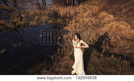 Bride with long hair and lake. View from above wedding shoot of beautiful girl in white dress on gorgeous autumn nature background