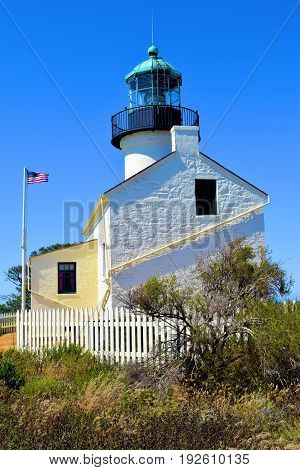 Point Loma Lighthouse which is a historical landmark opened in 1855 surrounded by coastal shrubs taken in Point Loma, CA