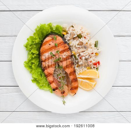 Grilled salmon steak and risotto on garnish top view. Healthy food, delicacy, lunch dish concept. White wooden planks background.