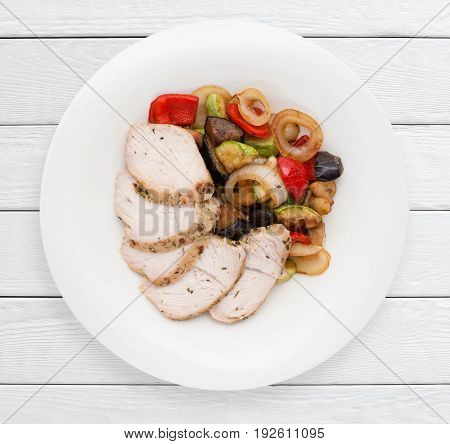 Boiled chicken fillet and vegetables grilled garnish. Healthy food, dietary meal, lunch dish concept. White wooden planks background.