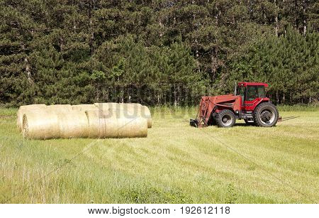 A farm tractor and round hay bales on a Wisconsin field.