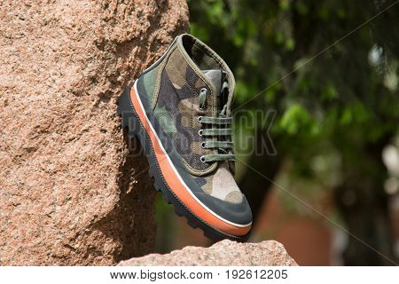 Camouflage shoes on a background of green grass