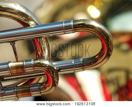 abstract backgrounds of brass band instruments with details of a trombone in the foreground