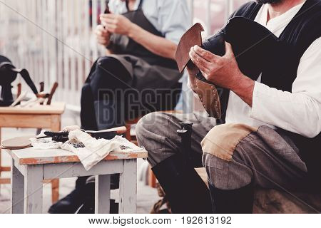 tailor master produces leather shoes. Concept of the old customs of making shoes and shoes.