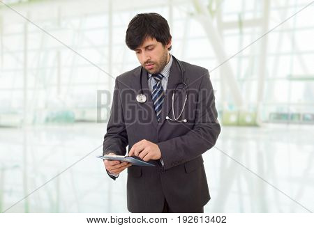 male doctor thinking with his notes, at the hospital