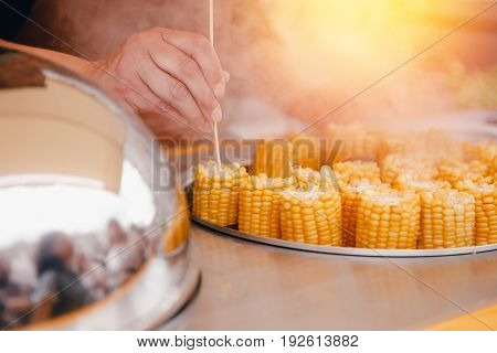 seller sells boiled yellow corn and salt outside the premises. Concept of street trading.