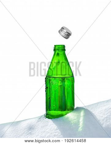 Open glass bottle of mineral water in snow
