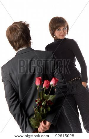 The young enamoured man with flowers and his girlfriend on a white background.