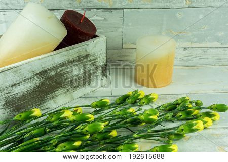 Rustic background of wood with candles and yellow carnations