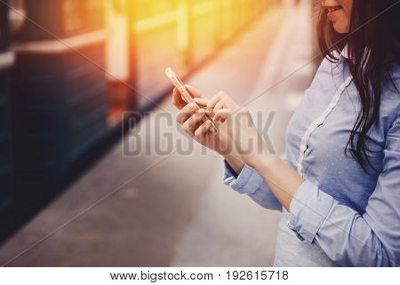 young tourist girl holds a phone, a means of communication, a fashionable gadget. The concept is always in touch.