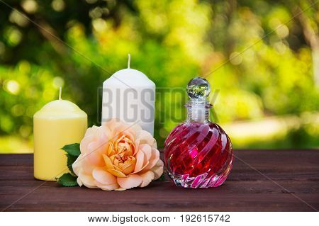 Fragrant rose oil in a beautiful glass bottle. Pink elixir candles and flowers. Spa concept. Romantic concept.
