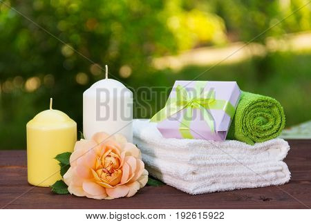 Stack of soft towels fragrant rose a candle and a small box with a gift. Spa concept. Romantic concept.