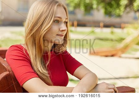 Sideways Portrait Of Pensive Young Female With Fair Hair Wearing Red Sweater Sitting Outdoors On Woo