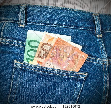 Euro banknotes sticking out of the back jeans pocket. Money for travel and shopping