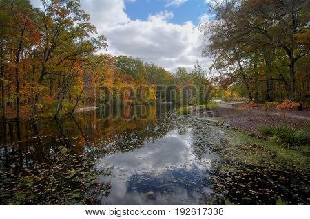 A beautiful autumn scene at a lake that shows the vibrant colors of autumn trees reflecting in the water.