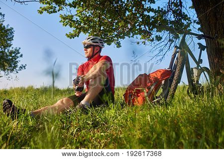 Attractive cyclist in the helmet sitting on the green meadow near the cycle in the countryside. Young man dressed in the sportwear and sporty shoes, with sunglasses and backpack. Beautiful landscape. Concept of the healthy lifestyle.