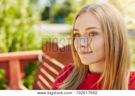 Pensive Woman With Sad Appealing Eyes, Freckled Pure Skin, Round Face And Blonde Hair Looking Aside