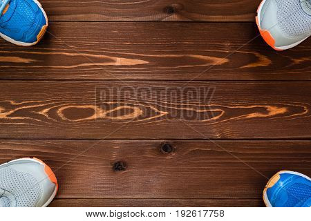 Fitness concept. Sport equipment. Sneakers (sport shoes) on wooden background.