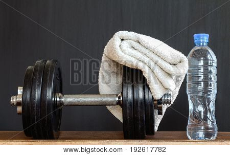 Fitness concept. Sport equipment.Towel bottle of water and dumbbells on black background.