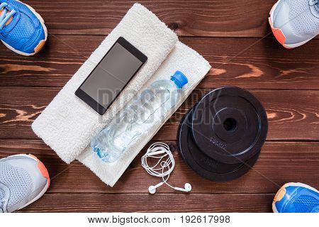 Fitness concept. Sport equipment. Sneakers (sport shoes) towel bottle of water earphones dumbbells and phone on wooden background.