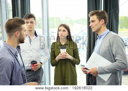 Group of young modern people in smart casual wear having a brainstorm meeting in the creative office